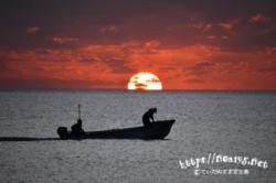 水平線に隠れる太陽と漁船