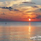 水平線に浮かぶ太陽とSUP