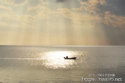 降り注ぐ光のシャワーと漁船