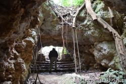 背をかがめて通る洞窟の出口-牧山陣地壕