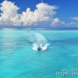 海の道を疾走するボートと入道雲