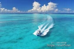 池間ブルーの海を疾走するボートと入道雲