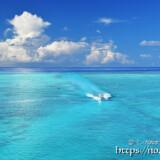 池間ブルーの海を走るボートと入道雲